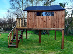 Imposing playhouse with staircase, balcony and swings