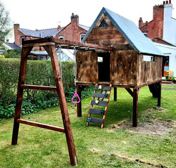 Pretty raised playhouse with porch, small balcony and slide