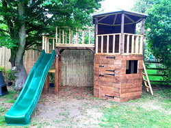 Hexagonal wooden playhouse with bridge, slide and monkey bars