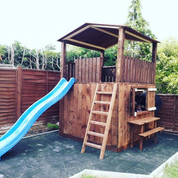 Double decker playhouse with slide, picnic bench and serving hatch