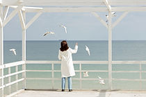 'Gull Therapy' radio drama by Anita Sullivan. Woman in white coat feeds seagulls.