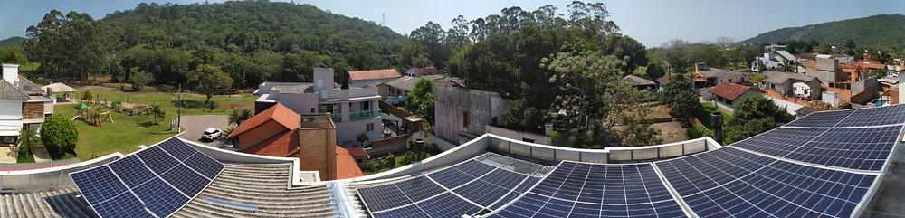 Placas solares sob telhado em duas partes para suprir a necessidade do cliente. Vista do telhado para outras residências locais.
