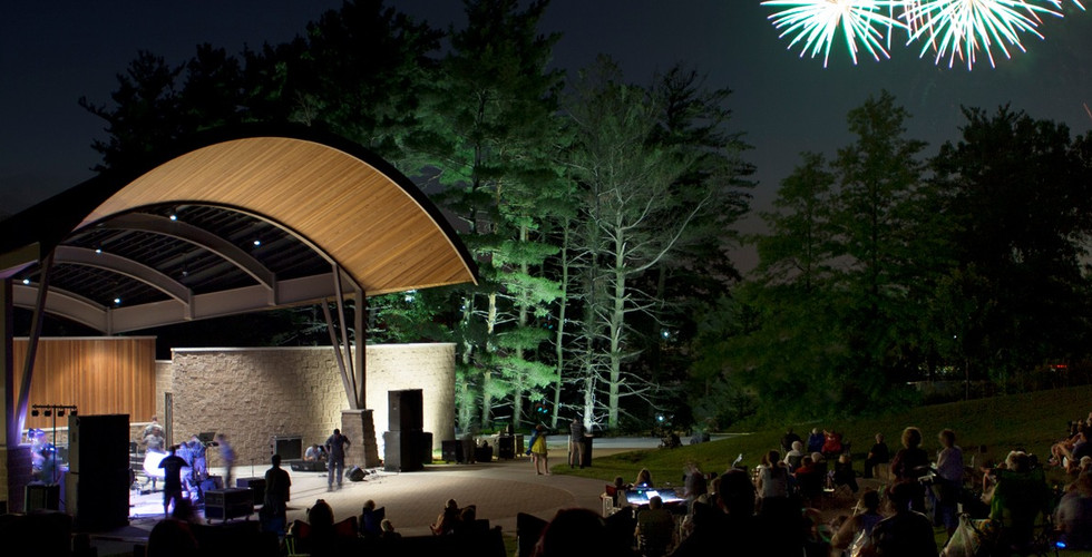 Barrel-vaulted bandshell supported by branching steel columns and sculptural stone walls creates new regional theatrical venue.