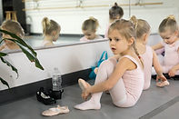 young girl putting on ballet shoes