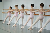 young girls dancing ballet at the barre