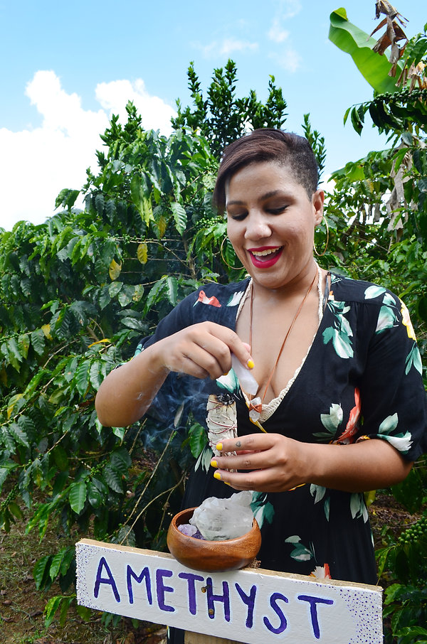 Beautiful woman practicing magic. Witch using sage and healing crystals in nature. Forest