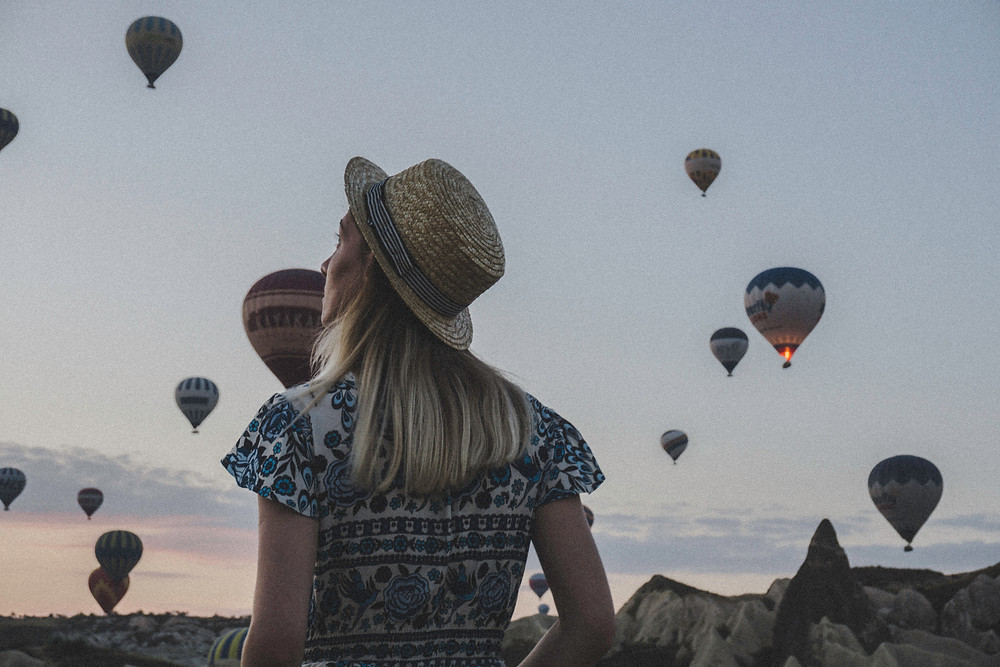 woman standing in front of air balloons