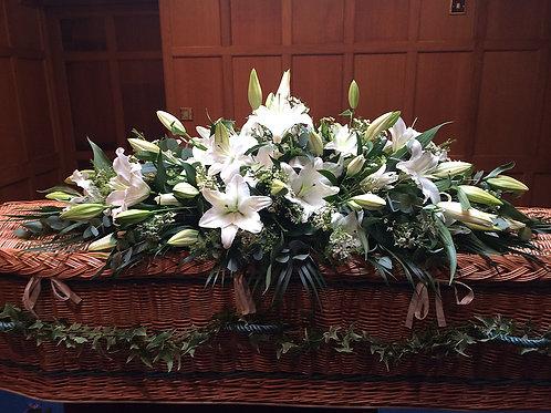 Lily casket spray dressed with ivy garland