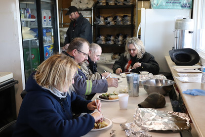 Volunteers enjoying a warm meal during event setup.