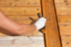 Painter staining deck boards with transp