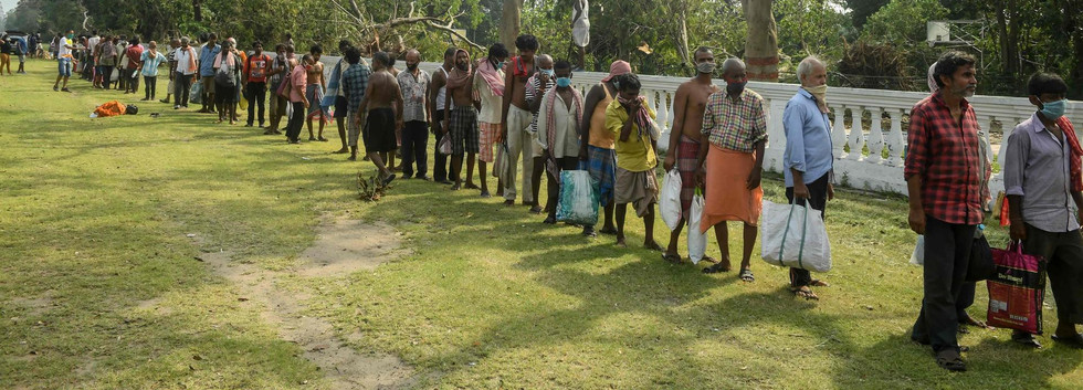 Migrant labourers queue to collect food distributed by locals at a roadside last month in Kolkata. Dibyangshu Sarkar / AFP