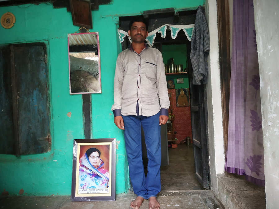 Ashish Kadu stands next to the photo of