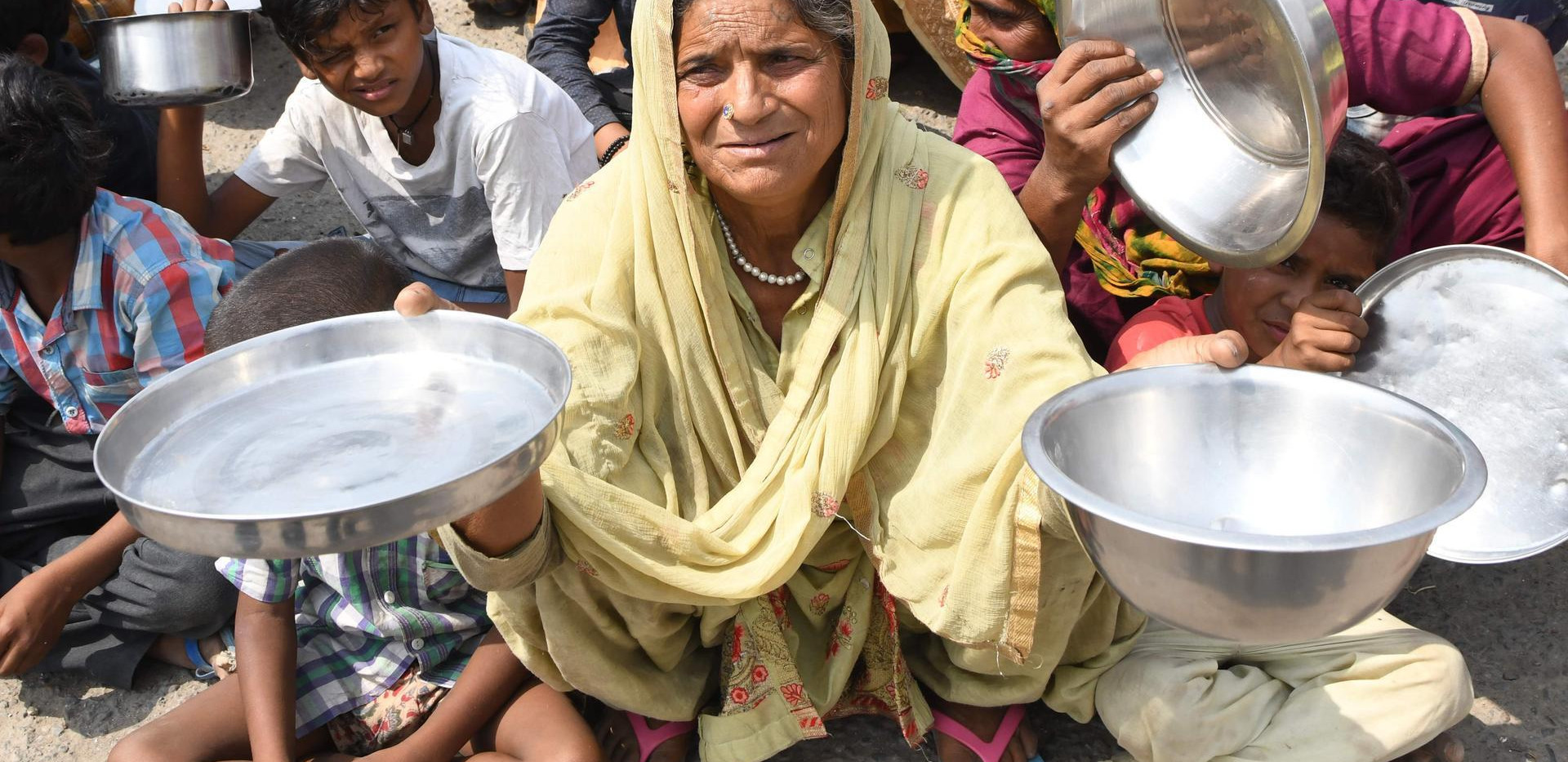 Families from Maharashtra hold out utensils to protest the lack of food in a slum area on the outskirts of Amritsar, Punjab, May 31. Narinder Nanu / AFP
