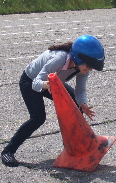 Girl picking up cone