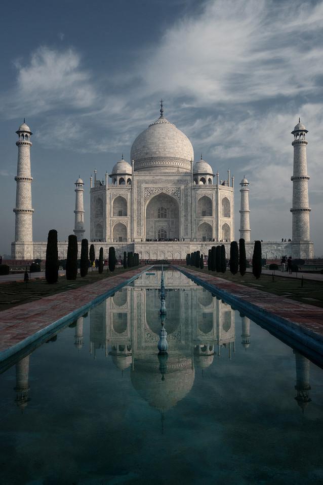 Architecture & Arts.  Editorial  TAJ MAHAL. Agra, India. Fotografía y texto: Jonathan Manrique Nossa  El deslumbramiento provocado por la construcción de mármol que brillaba frente a mí, reluciente y bella a la luz, reflejo de un dolor sufrido por la perdida de un gran amor, el Taj Mahal, me mantuvo por más de 12 horas observándolo atónito y encandelillado constantemente. Los matices de color y piedras preciosas incrustadas de manera tan profunda y delicada, que solo se hacen visibles en la oscuridad de su interior debido a la ayuda de las diminutas linternillas de los guías, vendrían a llevarme a entender la delicadeza y profundidad misma del sentimiento que motivó esta majestuosa construcción de principios del siglo XVII. Durante aquella visita al Taj Mahal, entre miles de personas que lo visitan hora a hora, pasé de ser un fotógrafo como cualquier otro a sospechoso por mi insistencia en la observación y apreciación de tan particular monumento, luego pasé a la amistad pasajera con los funcionarios del momento quienes se fueron acostumbrando a la presencia de mi mirada inquisitiva y enamorada. Finalmente se dio mi partida del lugar con una serie de imágenes atesoradas en la emoción y la mirada y que hoy me cuestionan sobre la proeza, potencia e impacto que puede generar en el mundo el sentimiento noble de amor que alberga el corazón de un ser humano.   Reflejo de un amor profundo, el Taj Mahal, ubicado en Agra, India, que ha sido declarado una de las siete maravillas del mundo y patrimonio de la humanidad por la UNESCO, es una oda arquitectónica al amor.   Durante el siglo XVII, en el sur de Asia, los profundos sentimientos del emperador Mughal Shah Jahan hacia su esposa, la princesa persa y musulmana llamada Mumtaz Mahal, fueron la semilla que inspiraron la construcción de esta maravilla arquitectónica. Ambos se conocieron a la edad de 14 años y se casaron 5 años después en el año de 1612. Casi 20 años después, en 1931 Mumtaz Mahal muere mientras da a luz a su dec