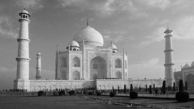 Architecture & Arts.  UNESCO Patrimony.   TAJ MAHAL. Agra, India. Fotografía y texto © Jonathan Manrique Nossa  El deslumbramiento provocado por la construcción de mármol que brillaba frente a mí, reluciente y bella a la luz, reflejo de un dolor sufrido por la perdida de un gran amor, el Taj Mahal, me mantuvo por más de 12 horas observándolo atónito y encandelillado constantemente. Los matices de color y piedras preciosas incrustadas de manera tan profunda y delicada, que solo se hacen visibles en la oscuridad de su interior debido a la ayuda de las diminutas linternillas de los guías, vendrían a llevarme a entender la delicadeza y profundidad misma del sentimiento que motivó esta majestuosa construcción de principios del siglo XVII. Durante aquella visita al Taj Mahal, entre miles de personas que lo visitan hora a hora, pasé de ser un fotógrafo como cualquier otro a sospechoso por mi insistencia en la observación y apreciación de tan particular monumento, luego pasé a la amistad pasajera con los funcionarios del momento quienes se fueron acostumbrando a la presencia de mi mirada inquisitiva y enamorada. Finalmente se dio mi partida del lugar con una serie de imágenes atesoradas en la emoción y la mirada y que hoy me cuestionan sobre la proeza, potencia e impacto que puede generar en el mundo el sentimiento noble de amor que alberga el corazón de un ser humano.   Reflejo de un amor profundo, el Taj Mahal, ubicado en Agra, India, que ha sido declarado una de las siete maravillas del mundo y patrimonio de la humanidad por la UNESCO, es una oda arquitectónica al amor.   Durante el siglo XVII, en el sur de Asia, los profundos sentimientos del emperador Mughal Shah Jahan hacia su esposa, la princesa persa y musulmana llamada Mumtaz Mahal, fueron la semilla que inspiraron la construcción de esta maravilla arquitectónica. Ambos se conocieron a la edad de 14 años y se casaron 5 años después en el año de 1612. Casi 20 años después, en 1931 Mumtaz Mahal muere mientras da a lu