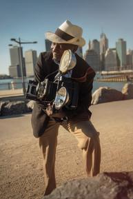 LOUIS MENDEZ  New York, USA  Es fotógrafo de la ciudad de New York City quien es conocido por su emblemática cámara de periodista, retratos y fotografia de calle.   Mendez usualmente usa una cámara Graflex Speed Graphic . Producida por Graflex en Rochester, Nueva York, la Speed Graphic comúnmente ha sido llamada la cámara de prensa más famosa. Aunque las primeras cámaras fotográficas de alta velocidad se produjeron en 1912, la producción de las versiones posteriores continuó hasta 1973