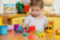 2 years old child playing plasticine in
