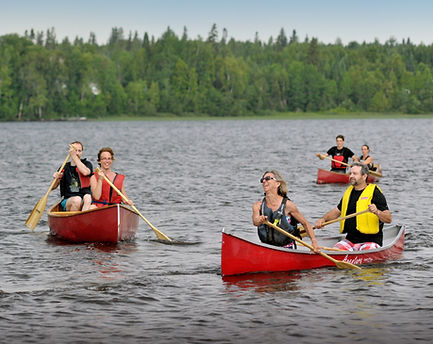 Groups experiencing the nomadic life of the First Nations in nature in canoes on Lake Quebec in summer