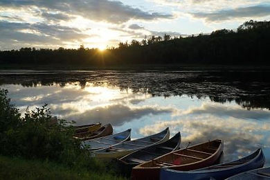 photo of a lake at sunset with traditional canoes anicinape Quebec landscape