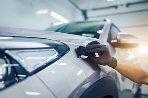 Car detailing - Man applies nano protective coating to the car. Selective focus..jpg