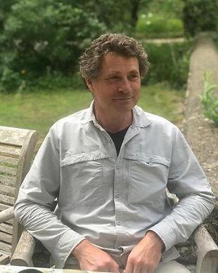 A profile image of author Rod Humphris. Caucasian male, short dark wavy hair, slim, sitting in a garden.