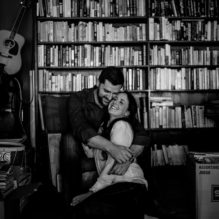 Black and white engagement photo in a bookstore in Glens Falls
