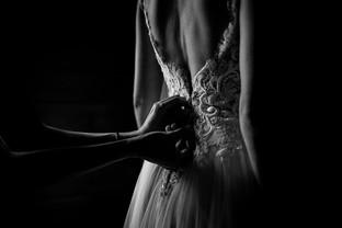 Moody photo of mother zipping up wedding dress