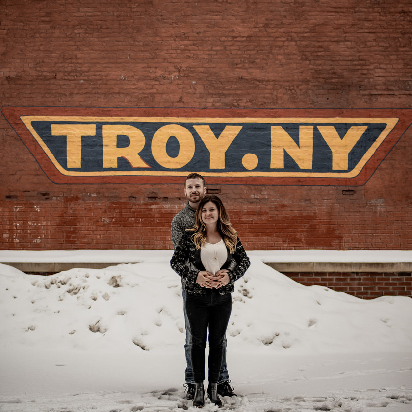 Couples photo in front of a Troy NY wall art backdrop