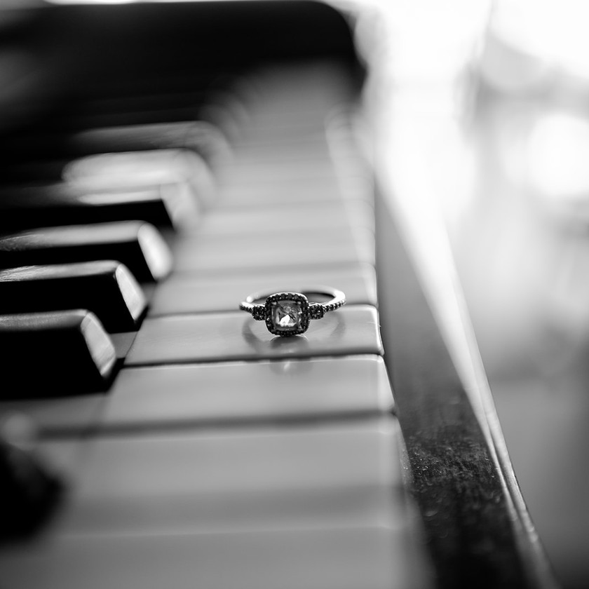 engagement ring on piano black and white