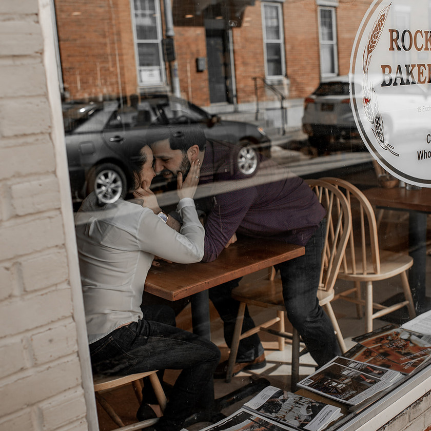 Intimate engagement photo through cafe window in Glens Falls NY