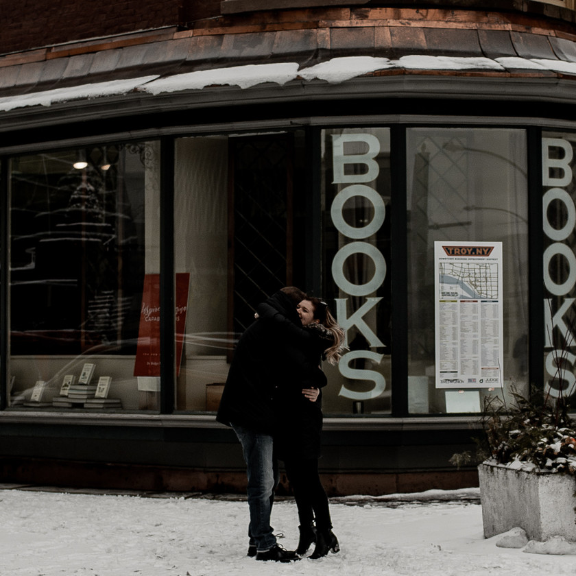 Couple hugging in downtown Troy for an engagement session