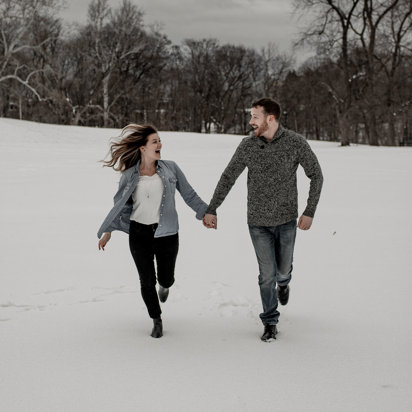 Couple running in the snow engagement photo pose
