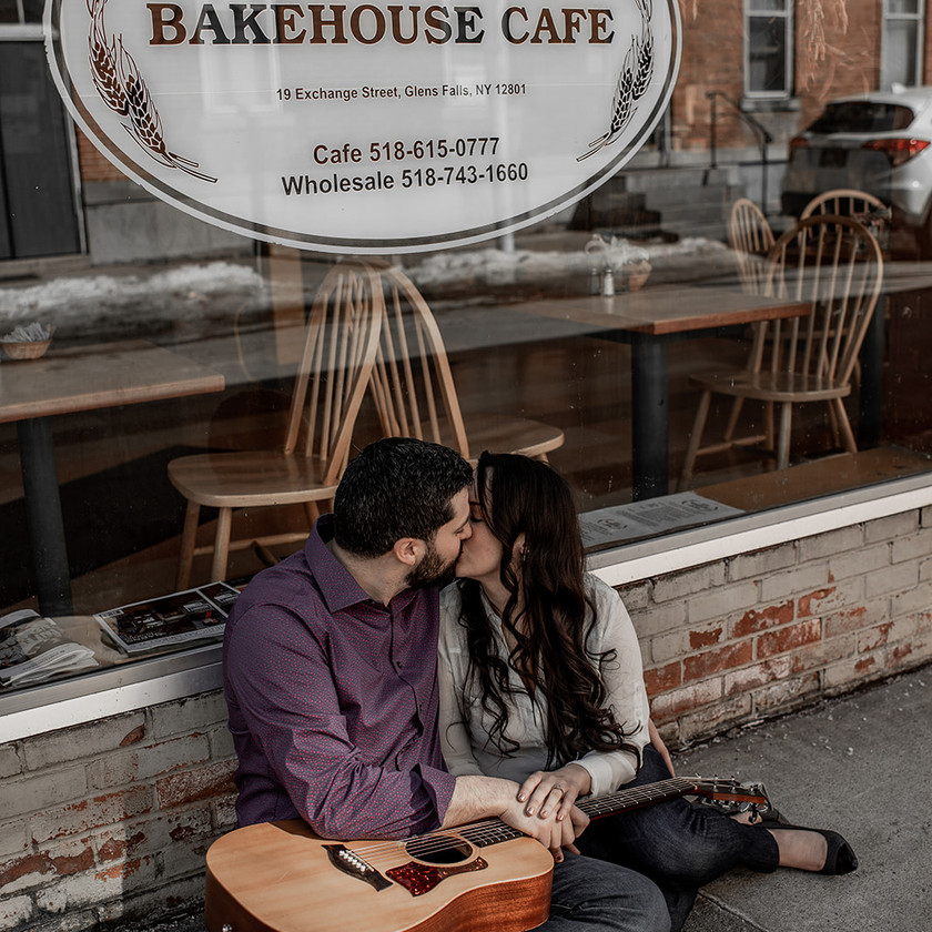 Couple kissing in front of a cute cafe in Glens Falls