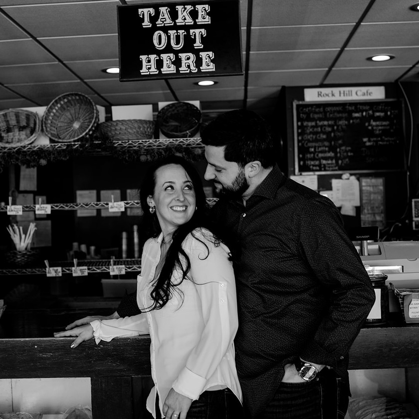 Black and white engagement photo in Glens Falls cafe