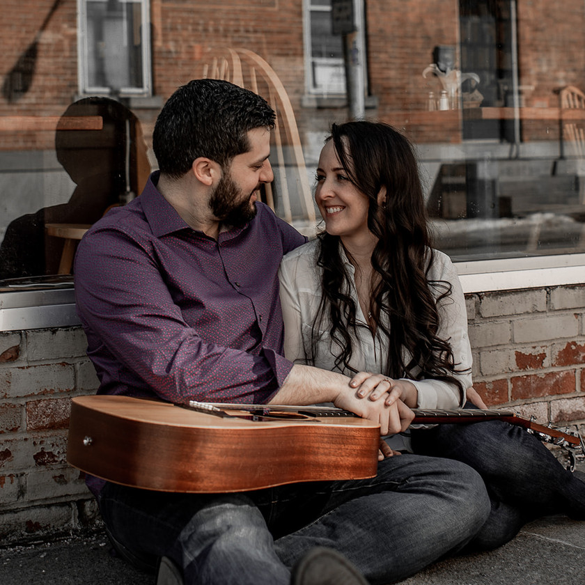 Couples photo with guitar in front of a cafe in Glens Falls NY