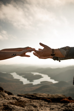 Reaching out hands on mountaintop engagement