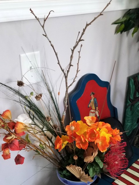 Stick in vase with dried and silk flowers.