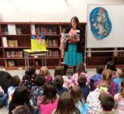 Micki Bare reading to a group of students during an author visit.