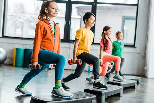 Preteen kids training with dumbbells and
