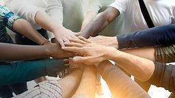 Diverse team joining their hands.jpg