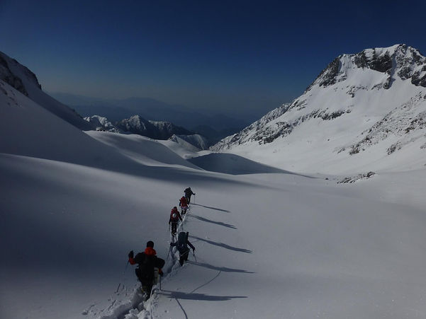 Climbers moving through snow filled valley between mountains