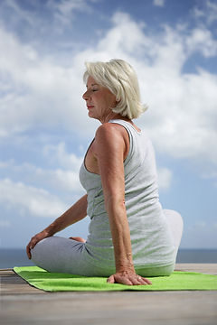 Middle-aged woman doing yoga outdoors.jp