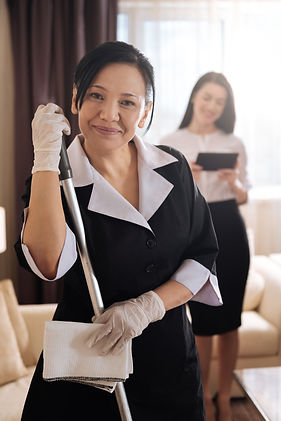 Nice delighted hotel maid holding a mop.