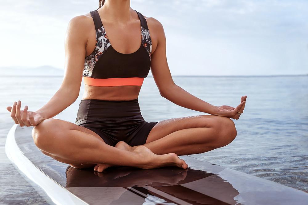 Femme faisant du yoga au bord de l'eau