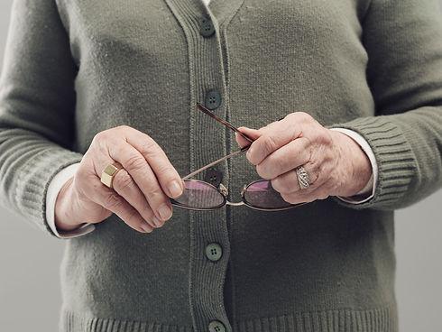 senior-lady-hands-holding-glasses-DLZ7JU