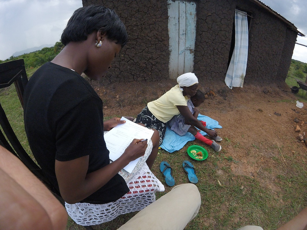 Global health worker recording interactions between mother and child.