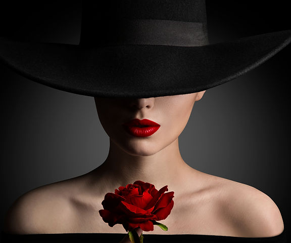 Woman in Hat holding Rose Flower in Hand