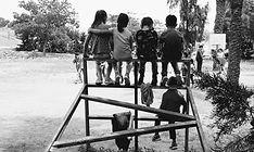 Fotografía de niñas y niños de espaldas sobre una estructura de hierros en blanco y negro
