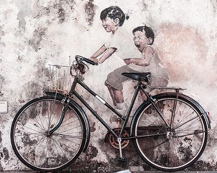 Grafiti de una niña y un niño disfrutando en una bicicleta